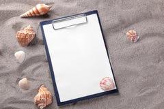 Una forma en blanco para registrar en la arena del mar con diversas cáscaras fotos de archivo