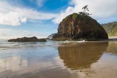 Una formación de roca de la pila del mar y un cielo azul hermoso con las nubes blancas que remolinan reflejadas sobre la arena mo foto de archivo
