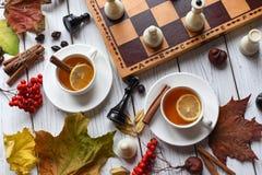 Una foto acogedora con dos tazas de té, tablero con el juego de ajedrez inacabado, hojas de otoño y palillos de canela Fotografía de archivo