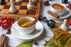 Una foto acogedora con dos tazas de té, tablero con el juego de ajedrez inacabado, hojas de otoño y palillos de canela Foto de archivo libre de regalías