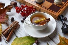 Una foto acogedora con dos tazas de té, tablero con el juego de ajedrez inacabado, hojas de otoño y palillos de canela Fotos de archivo