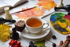 Una foto acogedora con una taza de té, de acuarelas, de un dibujo, de un libro, de hojas de otoño y de palillos de canela Imagenes de archivo