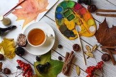 Una foto acogedora con una taza de té, de acuarelas, de un dibujo, de un libro, de hojas de otoño y de palillos de canela Imagen de archivo