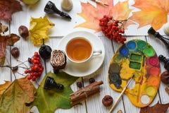 Una foto acogedora con una taza de té, de acuarelas, de un dibujo, de un libro, de hojas de otoño y de palillos de canela Fotografía de archivo libre de regalías