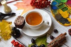 Una foto acogedora con una taza de té, de acuarelas, de un dibujo, de un libro, de hojas de otoño y de palillos de canela Imagen de archivo libre de regalías