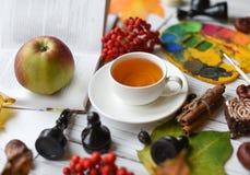 Una foto acogedora con una taza de té, de acuarelas, de un dibujo, de un libro, de hojas de otoño y de palillos de canela Imágenes de archivo libres de regalías