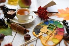 Una foto acogedora con una taza de té, de acuarelas, de un dibujo, de un libro, de hojas de otoño y de palillos de canela Foto de archivo libre de regalías