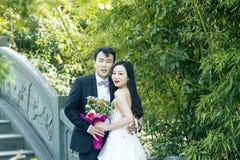 Una foto china de la boda del ` s de los pares que se coloca en un puente antiguo de piedra en parque de BO del shui en Shangai fotos de archivo libres de regalías