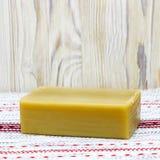 Una foto cuadrada del jabón orgánico hecho a mano natural del aceite de oliva en la tabla de madera Fondo rústico Accesorios del  Fotos de archivo