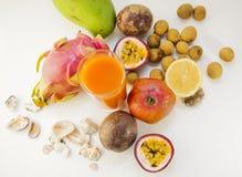Una foto de frutas tropicales y del jugo recientemente exprimido Mango, naranja, fruta de la pasión, papaya, fruta del dragón El  fotos de archivo libres de regalías