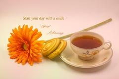 Una foto de la cita de la buena mañana con la taza de té, de flor y de galletas imagen de archivo