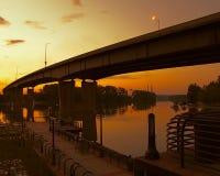 Una foto de la silueta de un puente y de un muelle hermoso en el agua con un cielo brillante del amarillo anaranjado en la puesta Imagenes de archivo