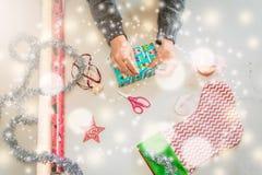 Una foto de las manos que envuelven los regalos de Navidad fotos de archivo libres de regalías