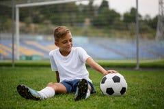 Una foto de un muchacho deportivo con una bola que se sienta en un campo verde en un fondo del estadio Actividades, concepto de l Fotos de archivo