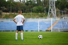 Una foto de un niño hermoso con una bola del fútbol en un fondo brillante del estadio Al aire libre actividades Copie el espacio Fotos de archivo