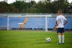 Una foto de un niño hermoso con una bola del fútbol en un fondo brillante del estadio Al aire libre actividades Copie el espacio Imagenes de archivo