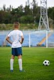 Una foto de un niño hermoso con una bola del fútbol en un fondo brillante del estadio Al aire libre actividades Copie el espacio Imagen de archivo