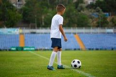 Una foto de un niño hermoso con una bola del fútbol en un fondo brillante del estadio Al aire libre actividades Copie el espacio Imágenes de archivo libres de regalías