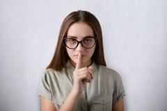 Una foto della ragazza attraente seria con i vetri d'uso del fronte sicuro e dei capelli diritti scuri che mettono il suo dito su Immagini Stock Libere da Diritti