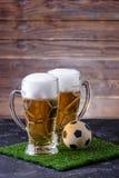 Una foto di due vetri di birra, pallone da calcio su erba verde Fotografie Stock Libere da Diritti