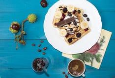 Una foto di due wafer viennesi, versata con cioccolato con le bacche ed il gelato su una tavola di legno sui bordi castagne, tè, immagine stock
