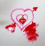 Una foto di tre cuori piccoli nel grande rosso immagini stock