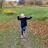 Una foto di un funzionamento sorridente della bambina su un percorso in un parco di autunno Fotografie Stock