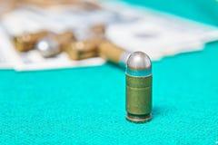 Una foto di una pallottola che sta sulla scacchiera fra i pezzi degli scacchi di menzogne Fotografia Stock