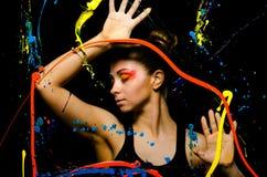 Una foto horizontal de una muchacha detrás de un vidrio pintado con la pintura Fotografía de archivo