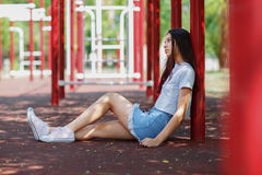 Una foto integral de un adolescente hermoso en ropa casual y gumshoes rosados que se sientan en una tierra del campo atlético Fotos de archivo