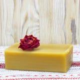 Una foto quadrata del fiore rosa romantico rosso asciutto e del sapone organico fatto a mano naturale dell'olio d'oliva sulla tav Immagini Stock
