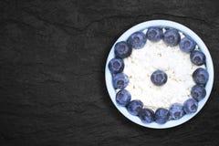 Una foto sopraelevata della ricotta naturale fresca con i mirtilli in una ciotola ceramica blu sul piatto di pietra nero Eco orga fotografia stock