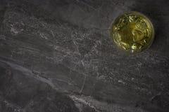 Una fotografía de arriba de un vidrio de whisky de oro con hielo en un fondo de mármol de la roca foto de archivo