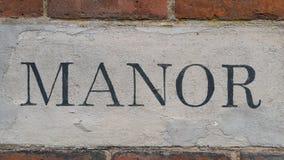 Una fotografía de la palabra de la casa señorial en una pared de ladrillo roja Foto de archivo libre de regalías