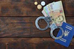 Una fotografia di un passaporto straniero ucraino, di una certa quantità di soldi ucraini e delle manette della polizia Concetto  immagine stock