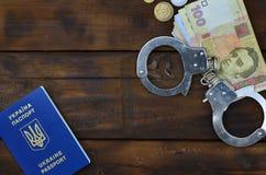 Una fotografia di un passaporto straniero ucraino, di una certa quantità di soldi ucraini e delle manette della polizia Concetto  fotografia stock