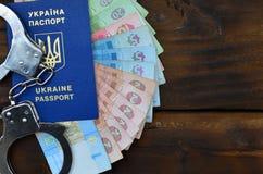 Una fotografia di un passaporto straniero ucraino, di una certa quantità di soldi ucraini e delle manette della polizia Il concet fotografie stock libere da diritti
