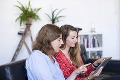 Una fotografia sopraelevata di due belle giovani donne a casa che si siedono fotografia stock libera da diritti