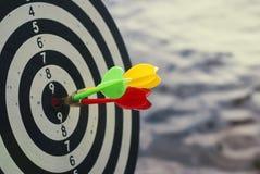 Una freccia sparata di tre dardi nel centro del bersaglio Concetto per mirare al successo ed al vincitore fotografia stock