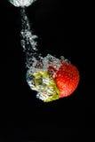 Una fresa que salpica en el agua foto de archivo libre de regalías