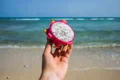 Una fruta del dragón en una mano en la playa Pitahaya Fruta tropical Imagen de archivo
