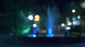 Una fuente con la iluminación coloreada del agua, por la tarde primer, falta de definición, 4k metrajes