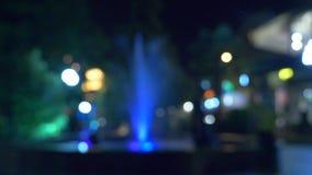 Una fuente con la iluminaci?n coloreada del agua, por la tarde primer, falta de definici?n, 4k almacen de metraje de vídeo
