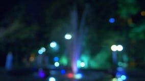 Una fuente con la iluminaci?n coloreada del agua, por la tarde primer, falta de definici?n, 4k almacen de video