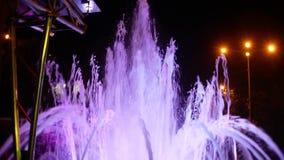 Una fuente con la iluminaci?n coloreada del agua, por la tarde Primer, 4K almacen de metraje de vídeo