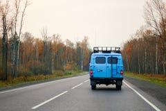 Una furgoneta azul que conduce en un camino a lo largo del bosque Foto de archivo libre de regalías