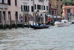 Una góndola y un barco que montan los canales de Venecia Foto de archivo
