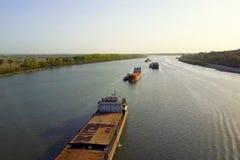 Una gabarra del cargo flota a lo largo del río Buque de carga imagen de archivo