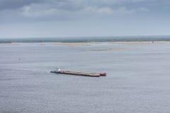 Una gabarra industrial lleva el cargo a través del río Una nave flotante Alzando, nave industrial Landsapes imagen de archivo libre de regalías