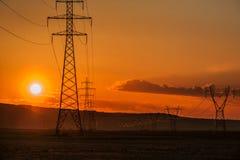 Torres de la línea eléctrica en la puesta del sol Imágenes de archivo libres de regalías